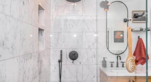 black shower head on white ceramic wall tiles