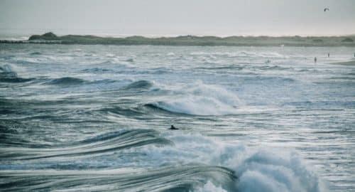 ocean waves under white sky during daytime